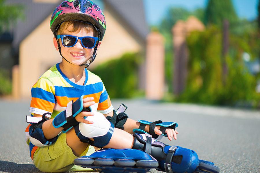 Cute little boy in helmet posing with rollers